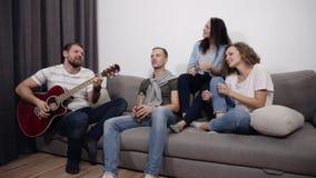 Il metraggio accelerato di una società di quattro amici si siede sul sofà ed ascolta il tipo che gioca la chitarra acustica Riuni stock footage