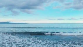 Il metraggio aereo di bello paesaggio della spiaggia dell'oceano con acqua blu, cielo nuvoloso variopinto impressionante, spumant stock footage