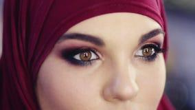 Il metraggio alto vicino del movimento lento di un hijab d'uso della ragazza che la apre occhi con affumicato variopinto perfetto archivi video