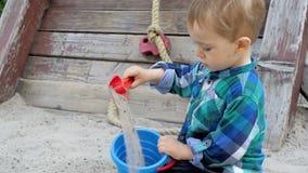 Il metraggio del movimento lento di scavatura bionda sveglia del ragazzo del bambino insabbia con la pala di plastica del giocatt archivi video