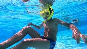 Il metraggio subacqueo di un bambino nuota in uno stagno subacqueo con una maschera stock footage