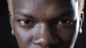 Il metraggio vicino del ` biondo dalla carnagione scura s dell'uomo osserva esaminando la macchina fotografica, isolata su fondo  stock footage