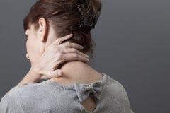 Il mezzo è invecchiato con signora di dolore al collo o della parte posteriore che si massaggia Immagine Stock
