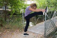 Il mezzo biondo della donna è invecchiato allungando le gambe in un parco Immagine Stock