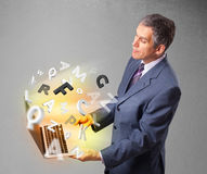 Il mezzo ha invecchiato il computer portatile della tenuta dell'uomo d'affari con le lettere variopinte Immagini Stock Libere da Diritti