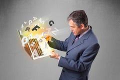 Il mezzo ha invecchiato il computer portatile della tenuta dell'uomo d'affari con le lettere variopinte Fotografia Stock