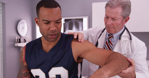 Il mezzo ha invecchiato il medico maschio che tratta l'i del giovane atleta adulto maschio Immagini Stock