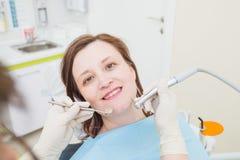 Il mezzo ha invecchiato il paziente della donna al dentista che perfora il dente con una turbina e che fa i materiali da otturazi immagini stock