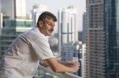Il mezzo ha invecchiato l'uomo al suo balcone che trascura il porticciolo Immagini Stock Libere da Diritti