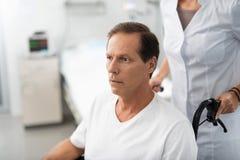 Il mezzo ha invecchiato l'uomo che si siede in sedia a rotelle alla stanza di ospedale fotografie stock