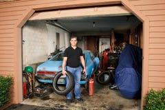 Il mezzo ha invecchiato l'uomo che sta nel garage stipato di che tiene una gomma Immagini Stock Libere da Diritti