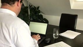 Il mezzo ha invecchiato l'uomo d'affari che lavora dalla casa sul computer portatile archivi video