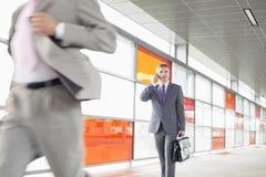 Il mezzo ha invecchiato l'uomo d'affari sulla chiamata mentre camminava nella stazione ferroviaria Fotografia Stock