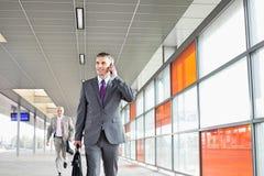 Il mezzo ha invecchiato l'uomo d'affari sulla chiamata mentre camminava nella stazione ferroviaria Fotografie Stock Libere da Diritti
