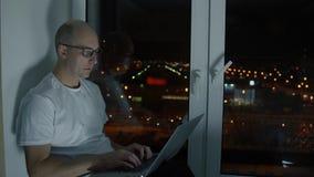 Il mezzo ha invecchiato l'uomo in occhiali che scrive sul computer portatile e che si siede sul davanzale stock footage