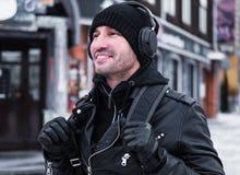 Il mezzo ha invecchiato l'uomo sorridente che cammina dalla via nell'orario invernale e che ascolta la musica tramite cuffie fotografia stock