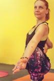 Il mezzo ha invecchiato l'yoga di pratica della donna sulla stuoia di esercizio Fotografia Stock