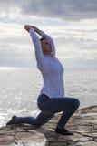 Il mezzo ha invecchiato la donna alla spiaggia che esegue l'yoga Fotografia Stock Libera da Diritti