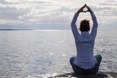 Il mezzo ha invecchiato la donna alla spiaggia che esegue l'yoga Immagini Stock Libere da Diritti
