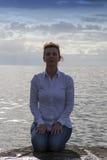 Il mezzo ha invecchiato la donna alla spiaggia che esegue l'yoga Immagine Stock
