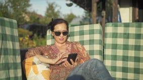 Il mezzo ha invecchiato la donna asiatica che utilizza lo smartphone nella sua iarda stock footage