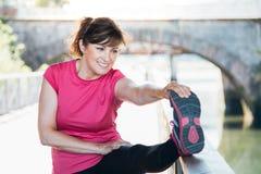 Il mezzo ha invecchiato la donna che allunga le gambe su una traccia fotografie stock libere da diritti