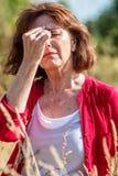 Il mezzo ha invecchiato la donna che ha rinite, allergie all'aperto Immagine Stock