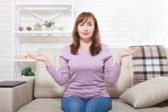 Il mezzo ha invecchiato la donna che si siede sui precedenti del sofà a casa Copi il giorno di madri e dello spazio menopause fotografie stock libere da diritti