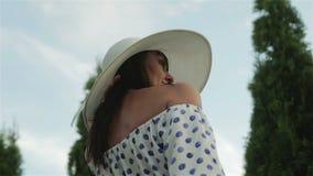 Il mezzo ha invecchiato la donna in un vestito ed il cappello bianco del sole sta guardando intorno, godendo del giorno soleggiat video d archivio