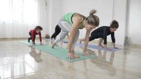 Il mezzo ha invecchiato la madre della donna che prende la sua piccola figlia ad una classe di yoga per praticare la posa del gue archivi video
