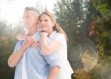 Il mezzo ha invecchiato le coppie che abbracciano nella foresta con il chiarore Immagine Stock Libera da Diritti