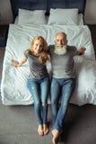 Il mezzo ha invecchiato le coppie che si siedono sul letto e sul sorridere immagini stock libere da diritti