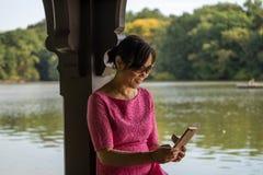 Il mezzo ha invecchiato il messaggio della lettura della donna sul suo telefono Fotografia Stock