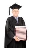 Il mezzo ha invecchiato professore dell'istituto universitario che tiene una pila di libri Fotografia Stock Libera da Diritti
