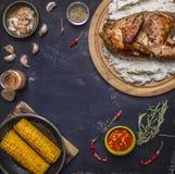 Il mezzo pollo con riso su un tagliere con le spezie, il mais e le erbe, posto per testo, incornicia la vista superiore del fondo Immagini Stock