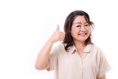 Il mezzo sicuro e riuscito ha invecchiato la donna che mostra il pollice su Immagini Stock Libere da Diritti