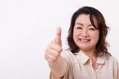 Il mezzo sicuro e riuscito ha invecchiato la donna che mostra il pollice su Fotografie Stock
