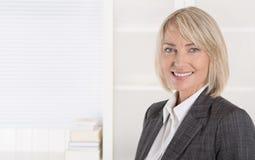 Il mezzo sorridente attraente ha invecchiato la donna di affari nell'uso del ritratto Immagini Stock Libere da Diritti
