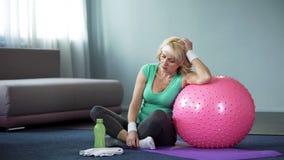 Il mezzo stanco ha invecchiato il rilassamento femminile sulla stuoia di yoga dopo l'allenamento domestico attivo, la dispnea immagine stock