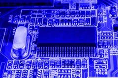 Il microchip ed il quarzo sulla scheda madre di un fondo blu del computer moderno chiudono la macro Immagini Stock Libere da Diritti