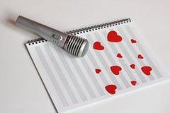 Il microfono ed i cuori rossi di carta sono posizionati su un taccuino pulito di musica Il concetto di musica e di amore Giorno d immagini stock libere da diritti