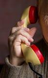 Il microtelefono è nella mano di una donna anziana fotografia stock libera da diritti