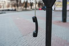 Il microtelefono appende sulla via su un cavo fotografia stock