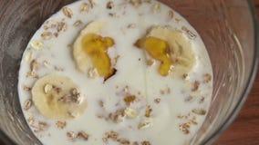 Il miele è versato dentro una ciotola di muesli, primo piano stock footage