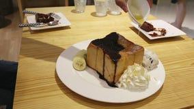 Il miele dei supporti di tazza della mano versa il gelato alla vaniglia e la banana del pane tostato archivi video
