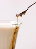 Il miele ha versato in latte con il cucchiaio Immagini Stock Libere da Diritti
