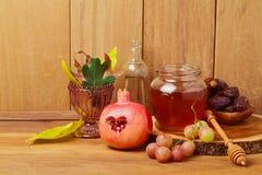 Il miele, il melograno, l'uva e l'autunno rimane il fondo di legno naturale Immagine Stock