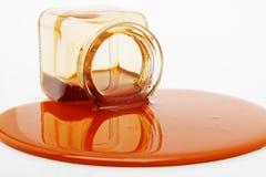 Il miele straripa un vaso di vetro Fotografia Stock