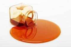 Il miele straripa un vaso di vetro Immagine Stock