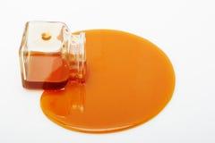 Il miele straripa un vaso di vetro Fotografie Stock